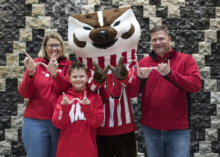 Business Badgers stand and smile with Bucky