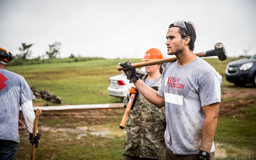 Jake Wood carrying a sledgehammer to work on disaster relief in the Bahamas