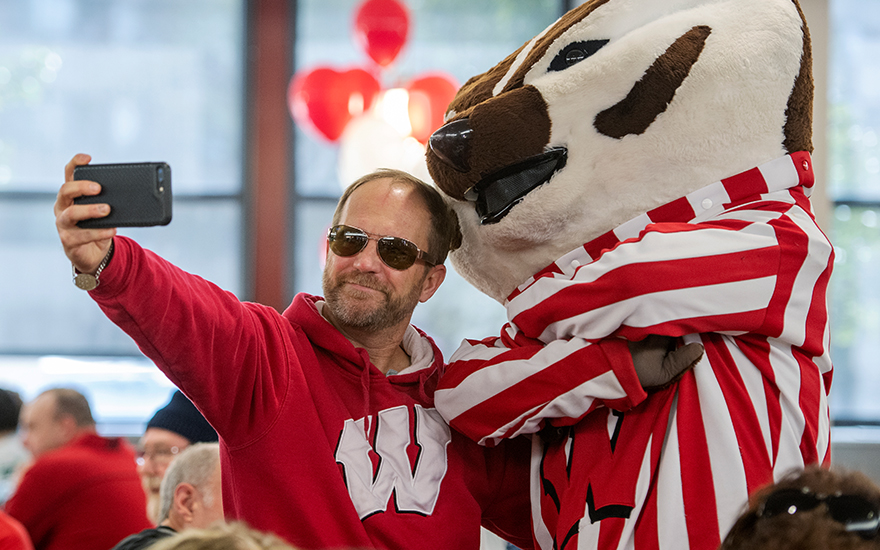 An alumnus posing for a selfie with Bucky Badger