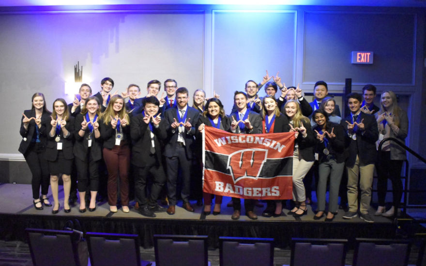 DECA regional competitors on stage holding UW-Madison flag