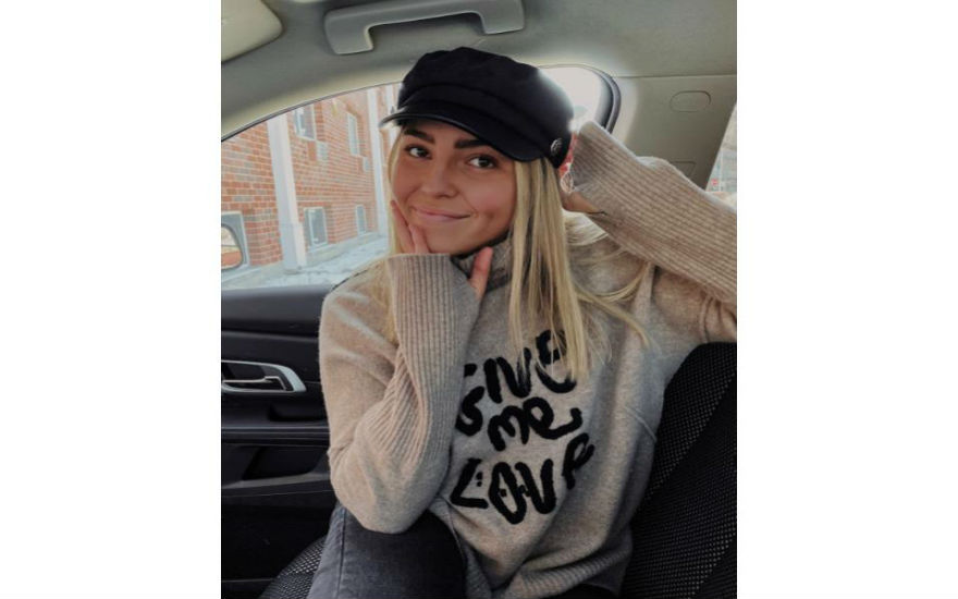 """Jade is wearing a black hat with an oatmeal colored sweater that says """"Give Me Love"""". Jade sits facing the camera in the passenger seat of a vehicle."""