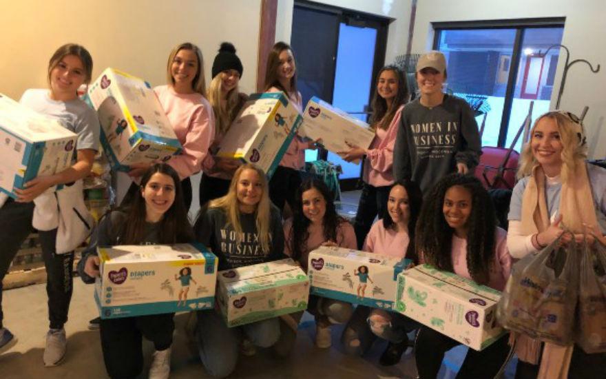 Women in Business members donating diapers
