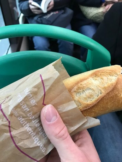 Hand holding a baguette