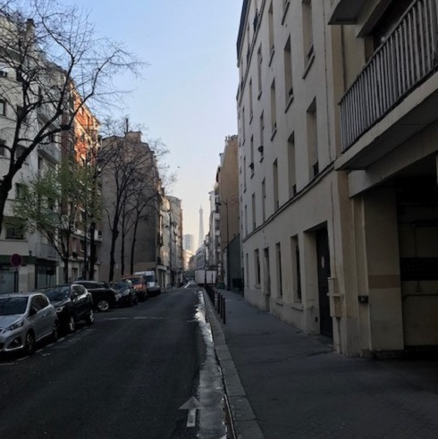 View down city street with Eiffel Tower in distance