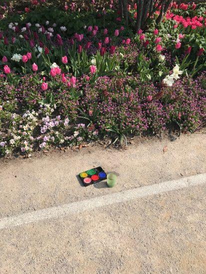 Paint set on sidewalk next to flower garden