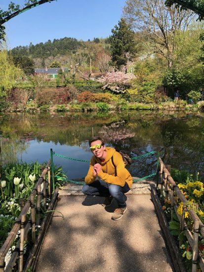 David kneeling in front of pond and nature landscape