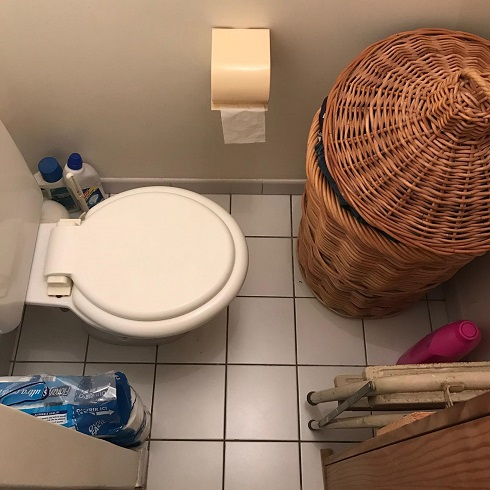 Host family toilet with clothes basket very close to the front of the toilet bowl