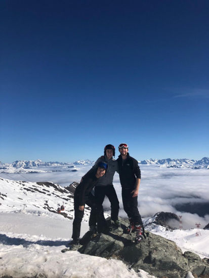 friends at the top of a ski hill