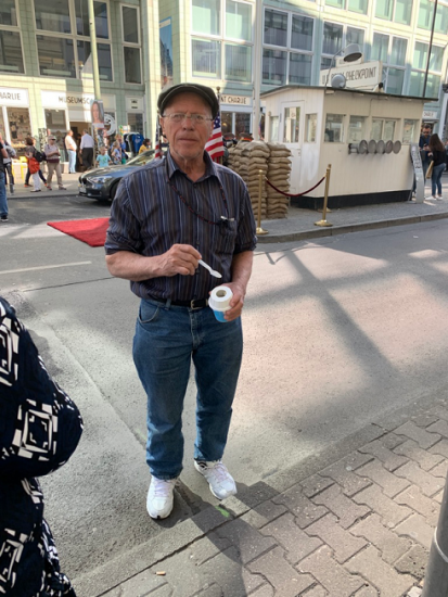 my grandfather eating a treat at Checkpoint Charlie