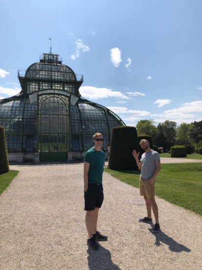Standing in front of a greenhouse