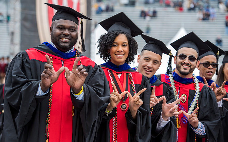 A group of Wisconsin MBA graduates proudly wear their cap and gowns.