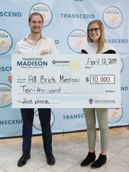 WAVE class alumni holding a giant check