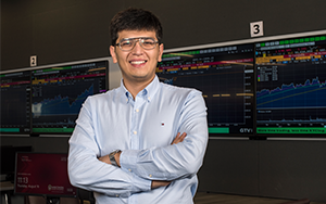 Ph.D. student Bekhzod Khoshimov stands in WSB's Finance Lab for a portrait