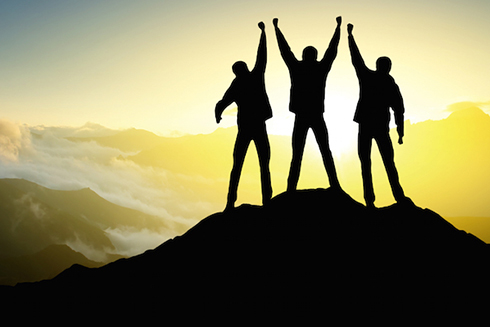 Three people on top of a mountain