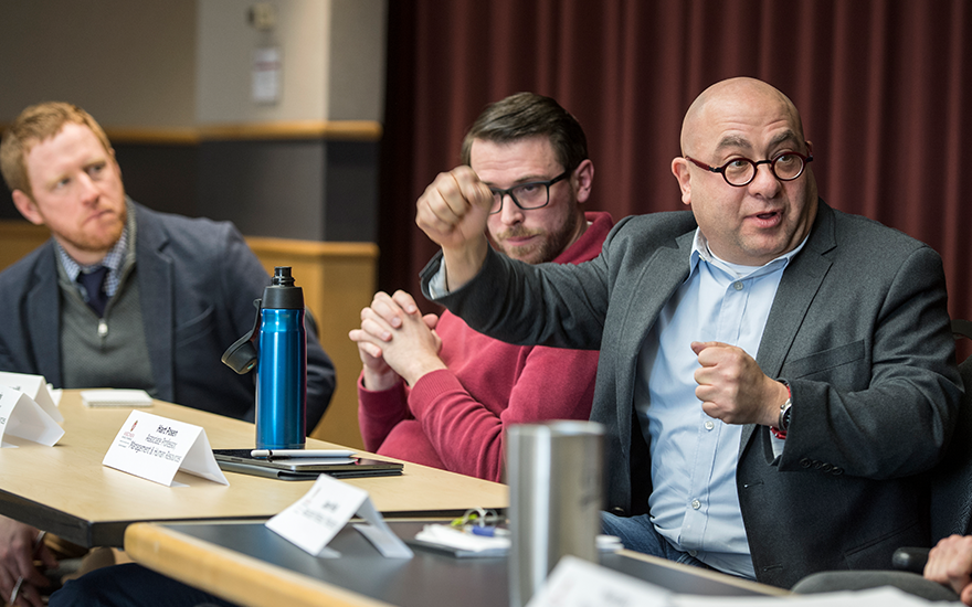 Hart Posen makes a point while seated on a faculty panel