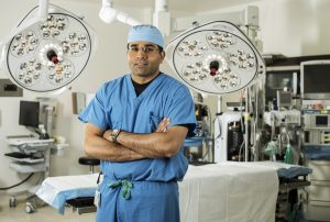 Surgeon wearing scrubs poses in a hospital