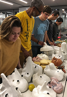 Students select from a row of masks in a class titled Performing Information.