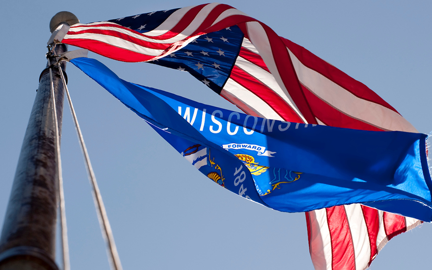 The United States flag and Wisconsin flag billowing together off a flag pole
