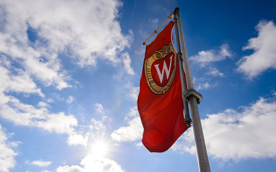 The UW-Madison crest appears on a flag waving in the wind.