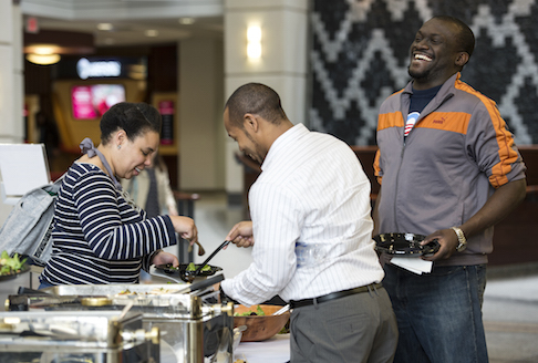 Ashligh Coaxum (MBA '16), left, and Justin Johnson (MBA '16), middle, grabs a bite to eat with Tosan Olley (MBA '15) and a hardy laugh before heading into a Lunch and Learn event on Wednesday, April 29, 2015.
