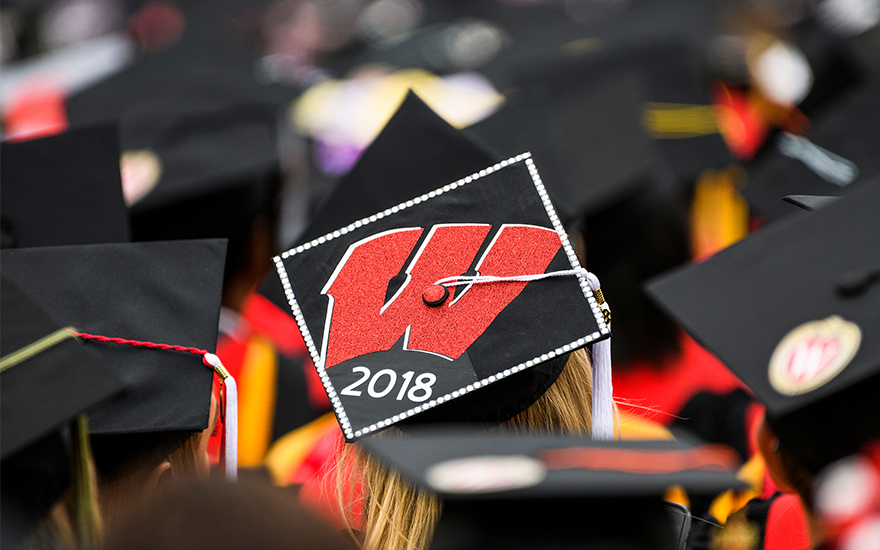An array of mortarboards sit atop the heads of UW-Madison graduates