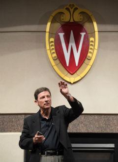 Bill Davis speaking in front of crest