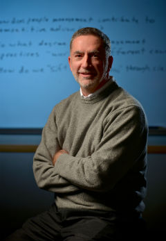 Barry Gerhart stands against a whiteboard with research