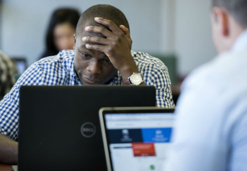 A student concentrates with head in hand in front of his laptop