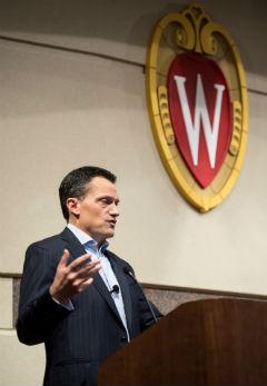 Alumnus John Peirson speaks under the UW crest