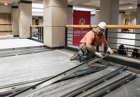 A construction worker lays building material inside Grainger Hall