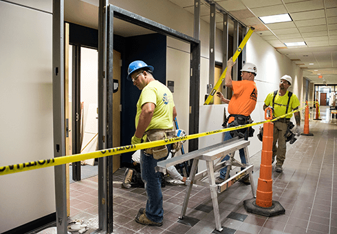 Three construction workers build temporary walls during the Learning Commons renovation