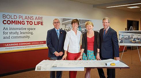Dean Massey, Ed Van Gemert, Sarah Mangelsdorf, and Steve Cramer standing over blueprints