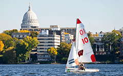 A UW-Madison sailboar slides across Lake Mendota on a warm summer day.