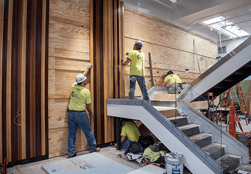 Construction workers install wood paneling in WSB's new Learning Commons.