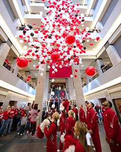 Students and alumni celebrate the Wisconsin Naming Gift announcement during a Homecoming celebration at Grainger Hall