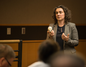 Natalie Rudolph holds 3D print object as she speaks to audience
