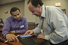 Enrique Rueda (right), multimedia coordinator at the Wisconsin School of Business, helps first-year Wisconsin Executive MBA student Joseph Koruth set up his new iPad Pro during the first day of class.
