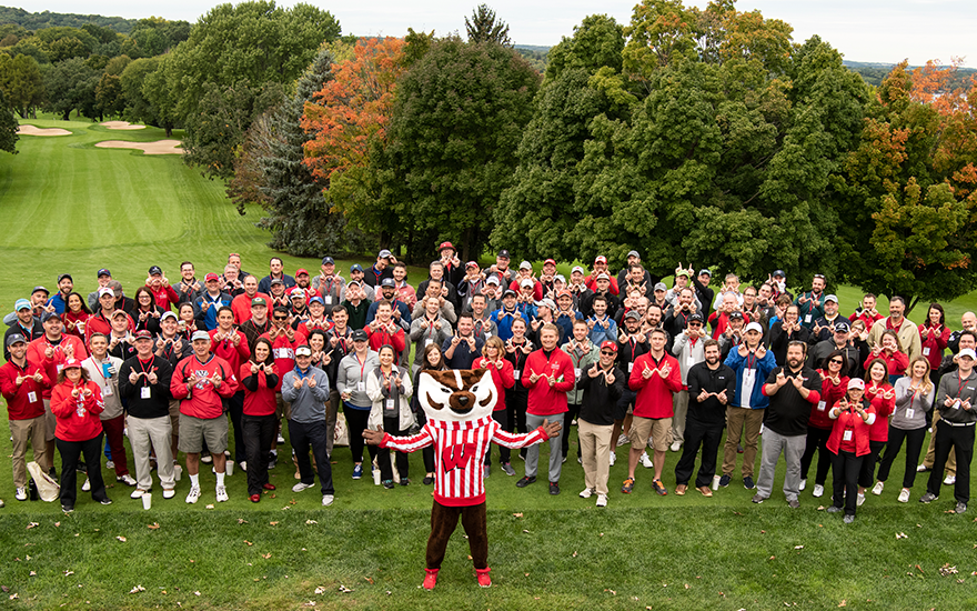 A large group of golfers and Bucky Badger pose for a group shot at the golf course.