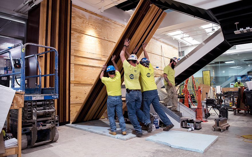A crew of construction workers lift a wall in WSB's new Learning Commons.
