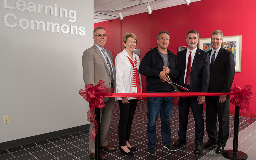 A group of University leaders pose for a ribbon cutting of WSB's Learning Commons.