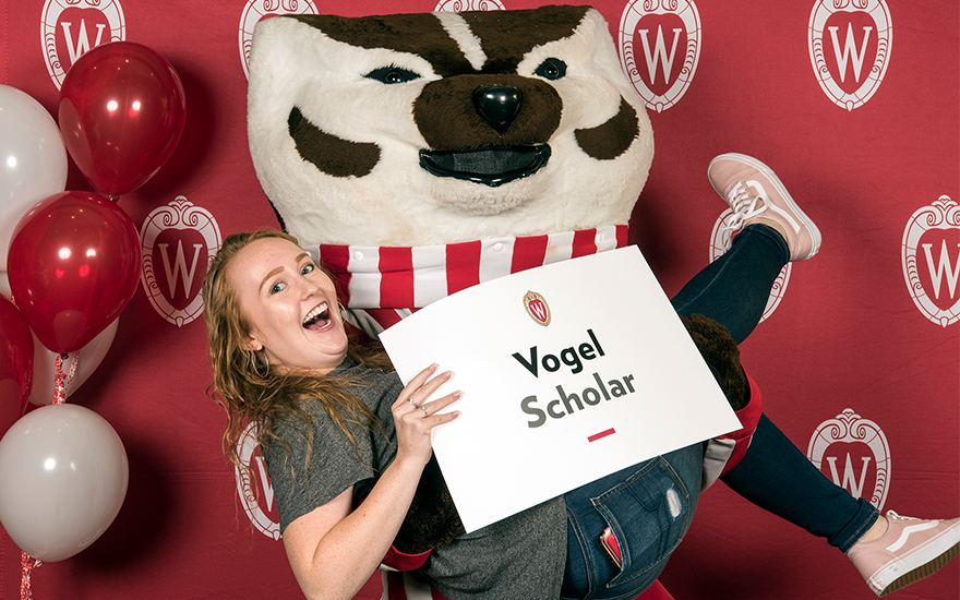 Bucky Badger holds a smiling female BBA student.