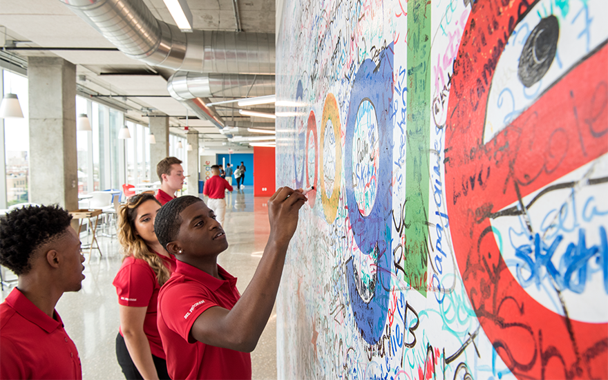 Students sign a wall with the Google logo at the company's office