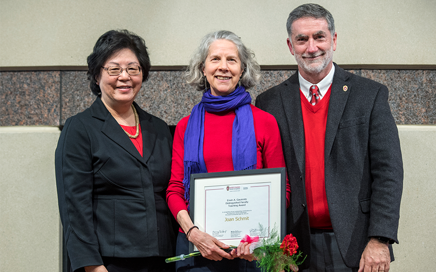 Professor Joan Schmit holds an award on stage with School leadership