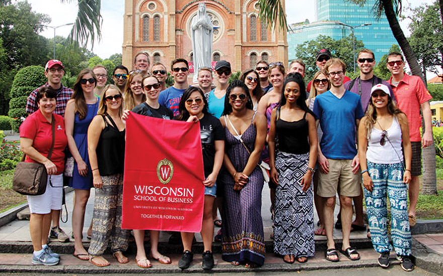 A group of MBA students hold a WSB flag in Vietnam