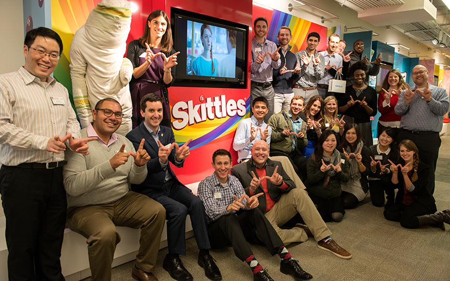 Students pose in front of a Skittles company display