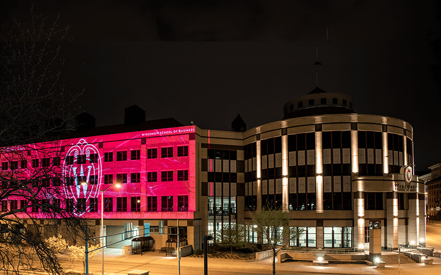 The exterior of Grainger Hall is illuminated with congratulatory messages for graduates