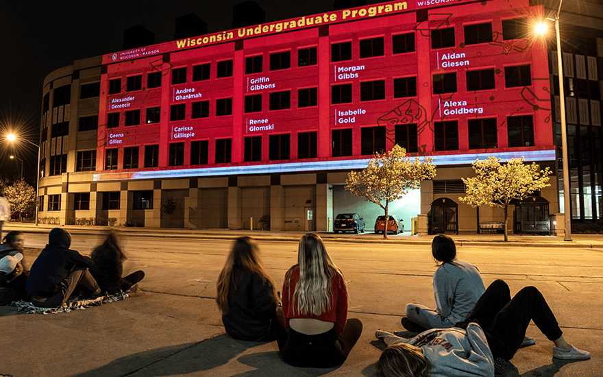 Passersby watch as the exterior of Grainger Hall is illuminated with congratulatory messages for graduates