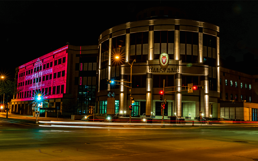 Grainger Hall is lit up in red to celebrate graduates.