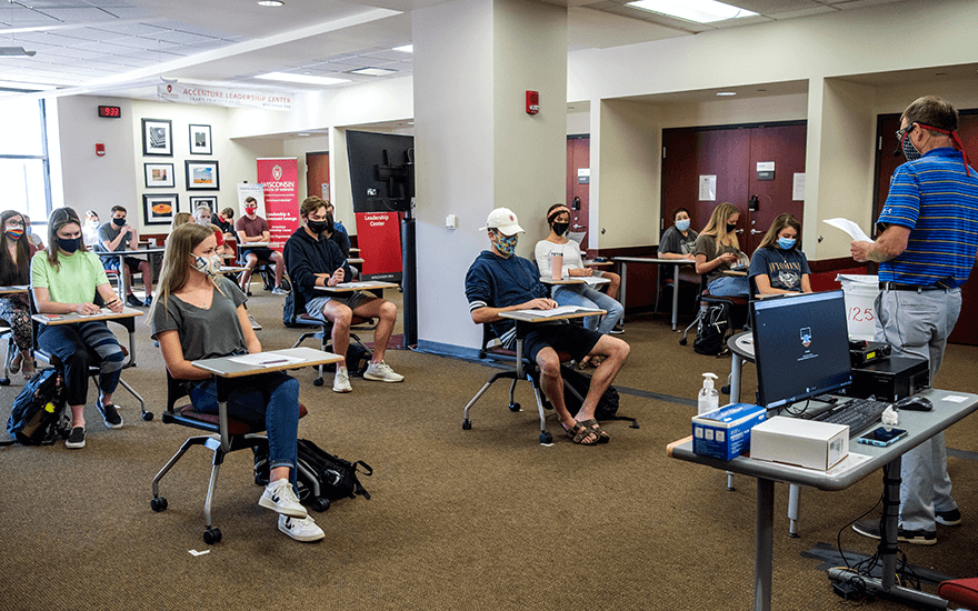 Students wearing masks sit six feet apart for a class at Grainger Hall