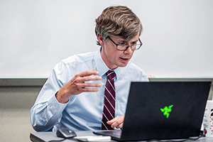 Lecturer Matt Griffith sits in front of his computer to teach an online course